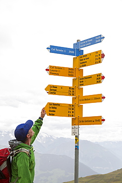 A hiker is looking at a sign post near Verbier. He is on his way on the Haute Raute, a classic multi day hike from Chamonix to Zermatt.