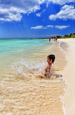 Photograph of young girl playing and bathing on beach of Caribbean Sea, Cozumel, Quintana Roo, Mexico