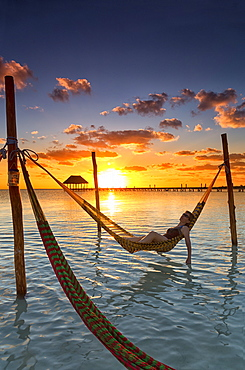 Woman lying in hammock at sunset, Holbox Island, Cancun, Yucatan, Mexico