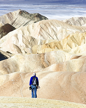 Rear view of a photographer at Zabriskie Point. Death Valley National Park, California.