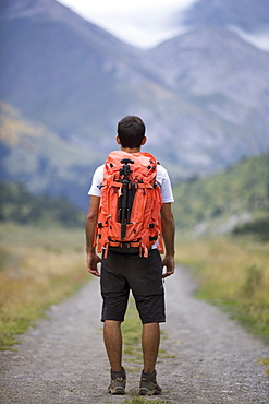 Rear view of male hiker standing with backpack on empty dirt road of Otal Valley, Torla, Huesca, Spain