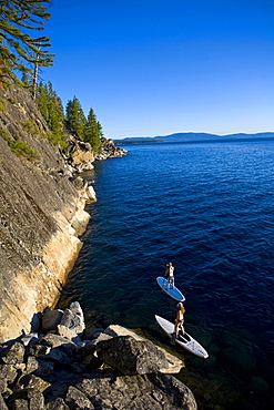 Man and woman paddleboarding near seashore, D.L. Bliss State Park, California, USA