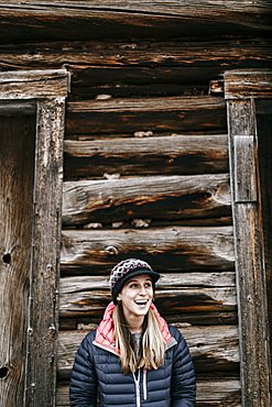 Waist up shot of smiling young woman in front of log cabin