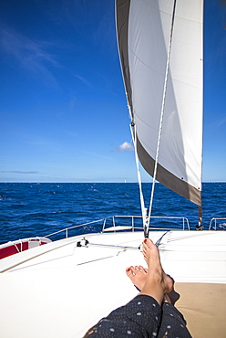 Low section view with feet of woman sunbathing on sailboat sailing in sea