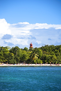 Scenic view of tourists on beach and lighthouse behind palm trees, Gosier, Guadeloupe