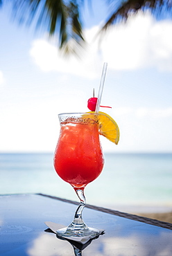 View of Caribbean tropical rum punch cocktail in glass on table against sea, Pink Gin Beach, Grenada