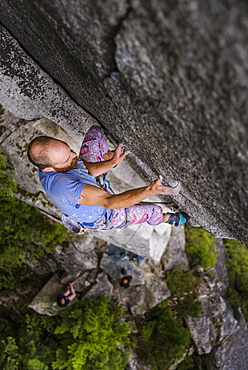 View from above of young man rock climbing, Squamish, British Columbia, Canada