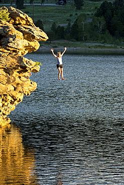 Adventurous woman jumping off rock into lake, Estes Park, Colorado, USA