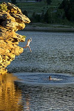 Adventurous girl jumping off rock into lake, Estes Park, Colorado, USA