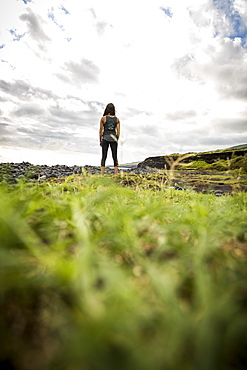 Rear view of lone woman with black hair standing in natural setting