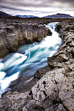 Scenic landscape of glacial meltwater running through andesite lava river channel in highlands of Iceland