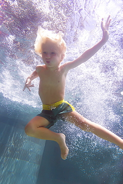 Underwater view of boy swimming in pool