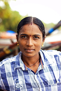 Head and shoulders portrait of mature woman with black hair looking at camera, Kerala, India