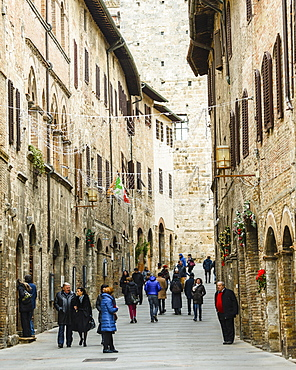 Tourists in San Gimignano, a small walled medieval hill town in the province of Siena, Tuscany, north-central Italy. Known as the Town of Fine Towers, San Gimignano is famous for its medieval architecture, unique in the preservation of about a dozen of its tower houses, which, with its hilltop setting and encircling walls