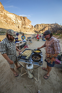 Two men cooking meal in outdoor kitchen during rafting trip, Desolation/Gray Canyon section, Utah, USA