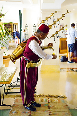 An Arabic man, dressed in traditional Ottoman style clothing, pours fruit juice from a large copper, adorned, spouted receptacle on his back, in a hotel lobby, Madaba Governorate, Jordan