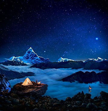 Starry sky over camper at bonfire on rock formation overlooking sea of clouds and mountains, Pokhara, Kaski, Nepal