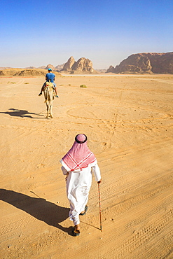 View of man in Arabic clothing walking through desert of Wadi Rum, protected desert wilderness in southern Jordan, with sandstone mountains and man riding camel in distance, Wadi Rum Village,  Aqaba Governorate, Jordan