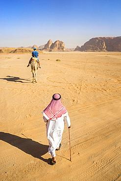 View of man in Arabic clothingwalking through desert of Wadi Rum, protected desert wilderness in southern Jordan, with sandstone mountains and man riding camel in distance, Wadi Rum Village, AqabaGovernorate, Jordan