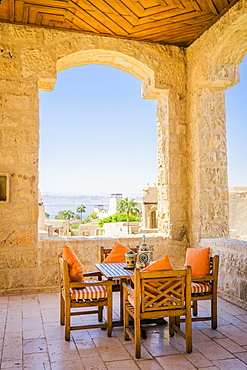 Table and chairs on covered terrace of Movenpick Dead Sea Spa and Resort with village in background, Madaba Governorate, Jordan