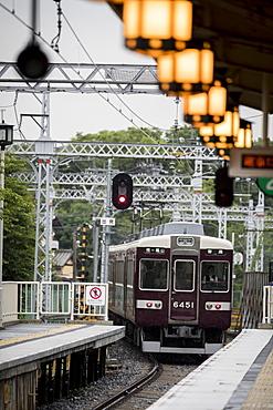Train departing from railroad station illuminated by glowing lanterns, Arashiyama, Kyoto, Japan