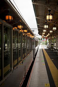 Train waiting at railroad station illuminated by glowing lanterns, Arashiyama, Kyoto, Japan