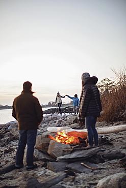 Group of friends enjoying time aroundbeachsidecampfire along coast, Peaks Island, Maine, USA