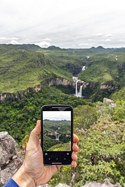 Hand holding mobile phone taking a picture of beautiful cerrado natural landscape with waterfalls in Mirante da Janela, Chapada dos Veadeiros, Goias, central Brazil