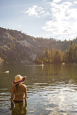Rear view of woman in bikini and with sun hat standing in lake, Shasta, California, USA