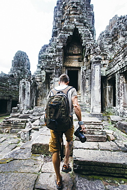 Rear view shot of a single tourist holding a camera exploring ancient Cambodian temple, Siem Reap Province, Cambodia