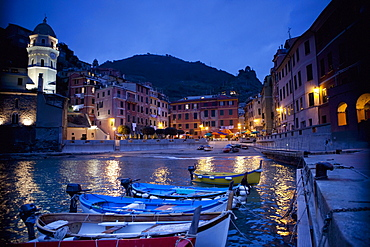 Boats Moored By Buildings Along The Waterfront At Night; Vernazza Liguria Italy