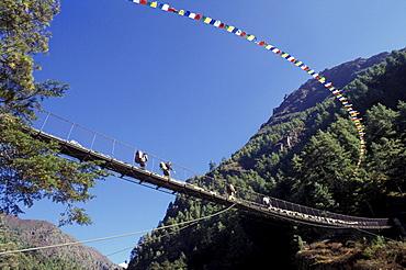 People Walking Across A Rope Bridge