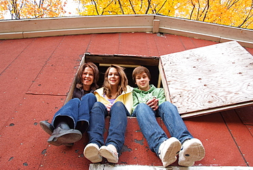 Mom with two teenagers sitting in the loft window of a barn, Simcoe, Ontario, Canada