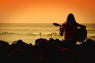 Woman Playing The Guitar And Looking Out To Sea