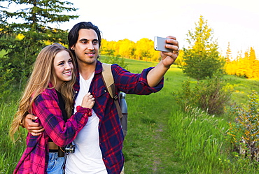 Young couple in a park posing for a self-portrait with their cell phone at sunset; Edmonton, Alberta, Canada