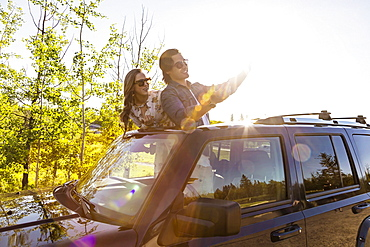 Young couple taking selfies with a cell phone in their vehicle; Edmonton, Alberta, Canada