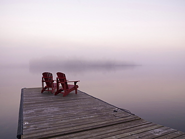 Two Red Adirondack Chairs On A Dock, Lake Of The Woods, Ontario, Canada