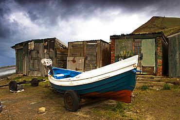 Boat Beside Old Shacks