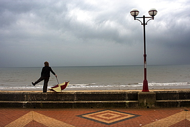 Man With Umbrella Standing By Boardwalk, Yorkshire, England