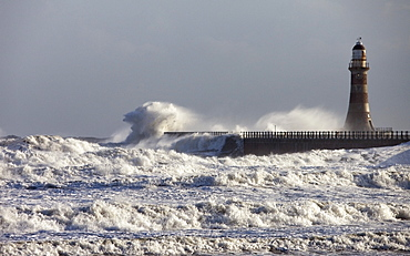 Waves Crashing Against A Pier With A Lighthouse