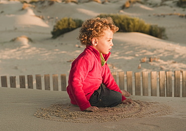 A Young Boy Playing On A Sand Dune, Tarifa, Cadiz, Andalusia, Spain