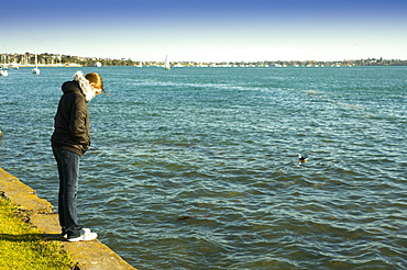 A Woman Standing On The Retaining Wall At The Water's Edge, Auckland, New Zealand