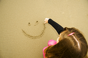 A Girl Draws A Happy Face In The Sand