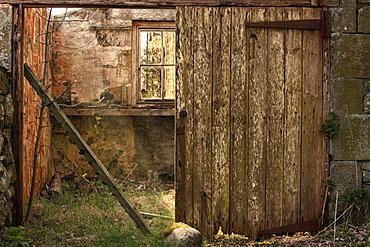 Northumberland, England, An Abandoned Building In Ruins With A Broken Wooden Door