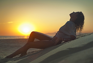 A Woman Wearing A Bathing Suit Lies On The Sand On Los Lances Beach At Sunset, Tarifa, Cadiz, Andalusia, Spain