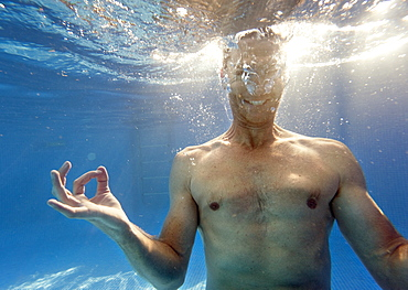 A Man Doing A Mediation Pose Under The Water, Benalmadena Costa, Malaga, Andalusia, Spain