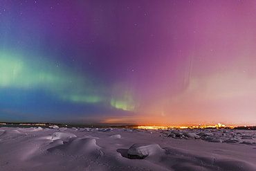 Northern lights shine above city skyline in this nighttime view from the tony knowles coastal trail in winter, Anchorage alaska united states of america