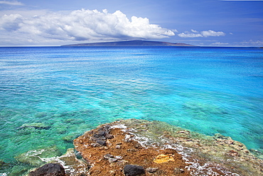A view of la perouse bay with clear water and coral with kooholawae in the distance, Maui hawaii united states of america