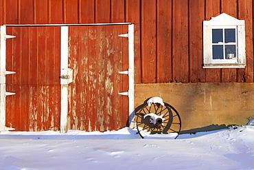 Old wagon wheel leaning against a red barn with freshly fallen snow on a farm near Edgewood in Northeast Iowa, Winter