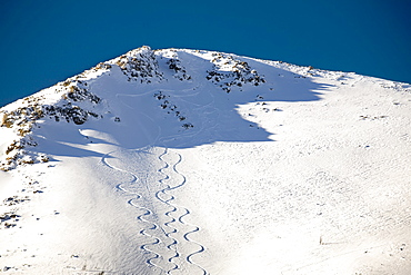 Snow covered mountain peak with skier tracks and deep blue sky, Lake louise alberta canada